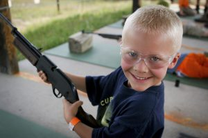 Boy happily (and safely) shoots a bb gun at camp.